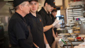 A line of employees stand behind a Costa Vida counter, ready to serve guests.