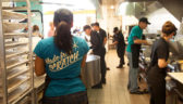 """A woman stands with her back to the camera wearing a blue shirt that says """"Made from Scratch"""" as other Costa Vida employees can be seen in the background preparing food and serving guests."""