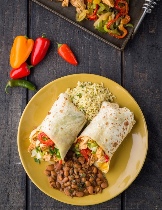 A yellow plate filled with a large burrito with a side of rice and beans. Nearby sit fresh, uncut peppers and freshly sauteed burrito stuffings.