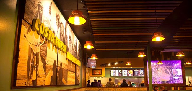 "The interior of a busy Costa Vida restaurant, with guests waiting in line, wall art that reads ""Costa Fresh Live Inspired"" and a purple-lit glass bubble wall with the Costa Vida wave logo."