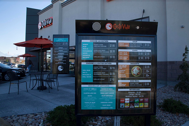 A Costa Vida drive-thru menu board, with the restaurant and an outdoor patio visible in the background.