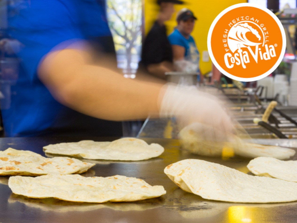 A blurred hand flips a tortilla as others can be seen cooking on a round, flat griddle. An orange Costa Vida logo is in the top-right of the image.