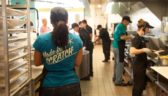 "The view from a Costa Vida kitchen looking out toward the prep line, with out-of-focus employees working the grills and serving guests. In the foreground, a woman with a ponytail stands with her back to the camera, the words ""Made from Scratch"" on the back of her shirt."